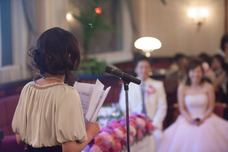 Woman standing at a microphone giving a speech at a wedding