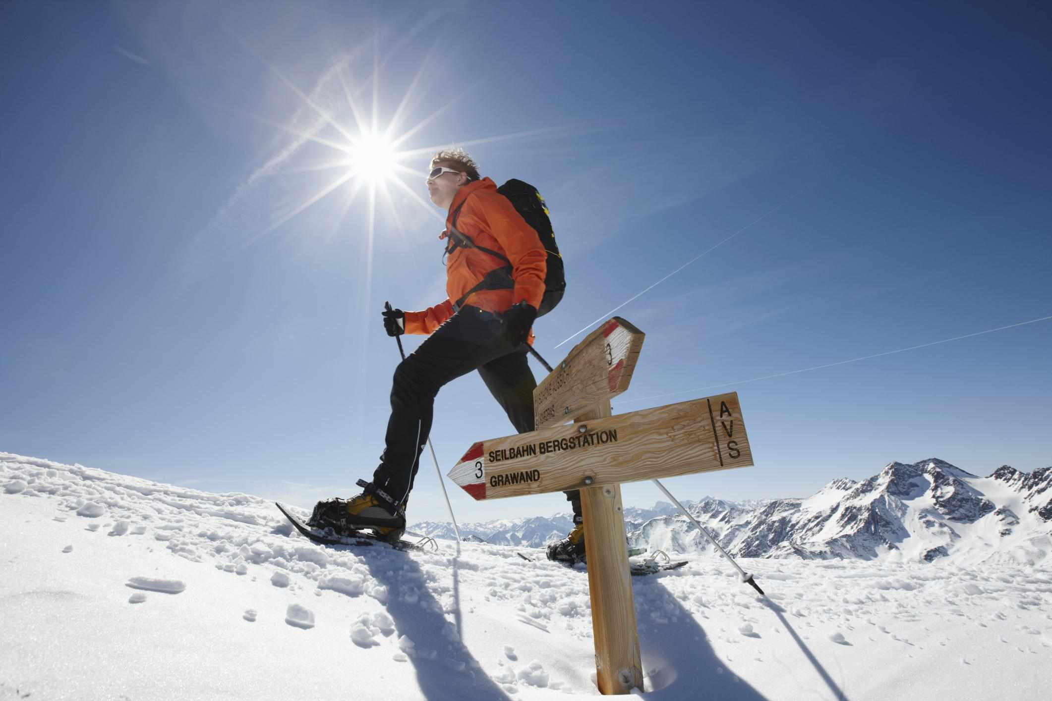 Man with snowshoes walking on a snowy mountain