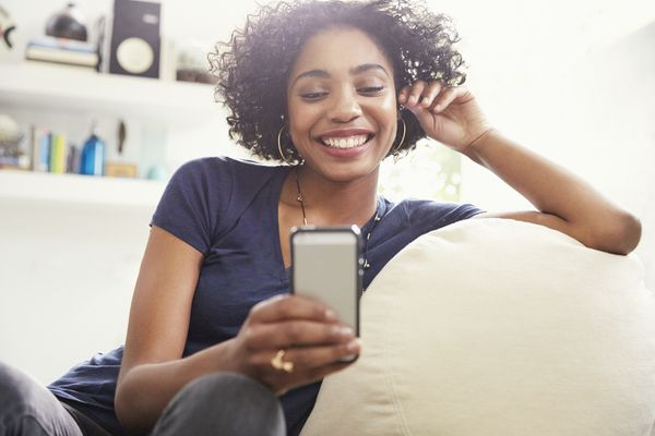 Smiling African American woman texting with cell phone on living room sofa