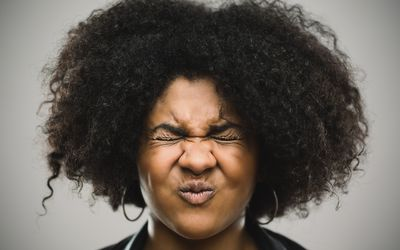 Close-up portrait of stressed real young afro american woman clenching eyes. Shocked female against gray background. Horizontal