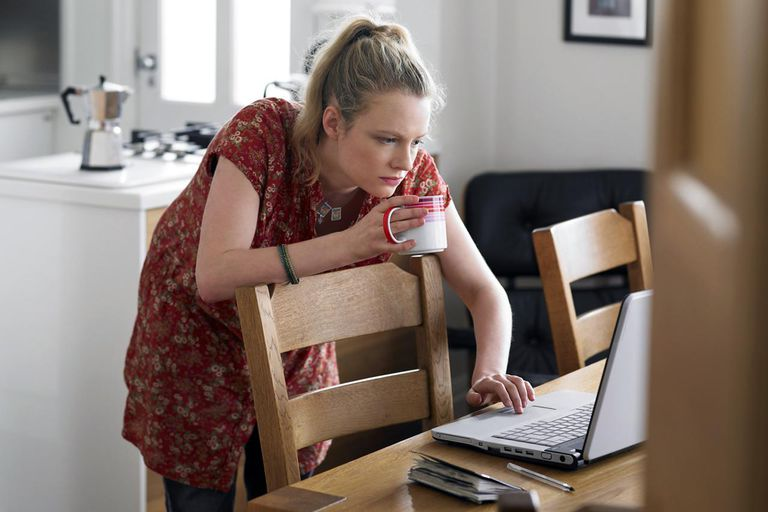 Woman using laptop on dining table, elevated view