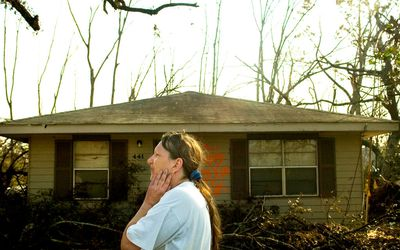 A woman surveying her property, which has been devastated by a hurricane.