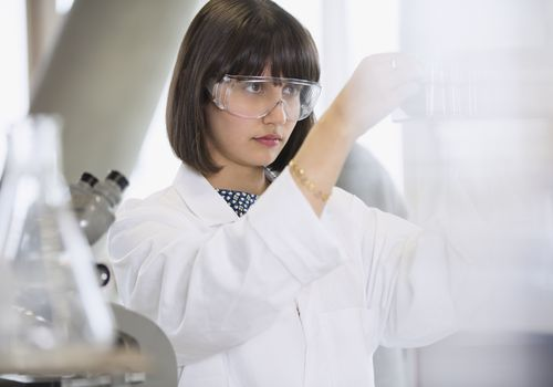 Female college student conducting scientific experiment in science laboratory classroom