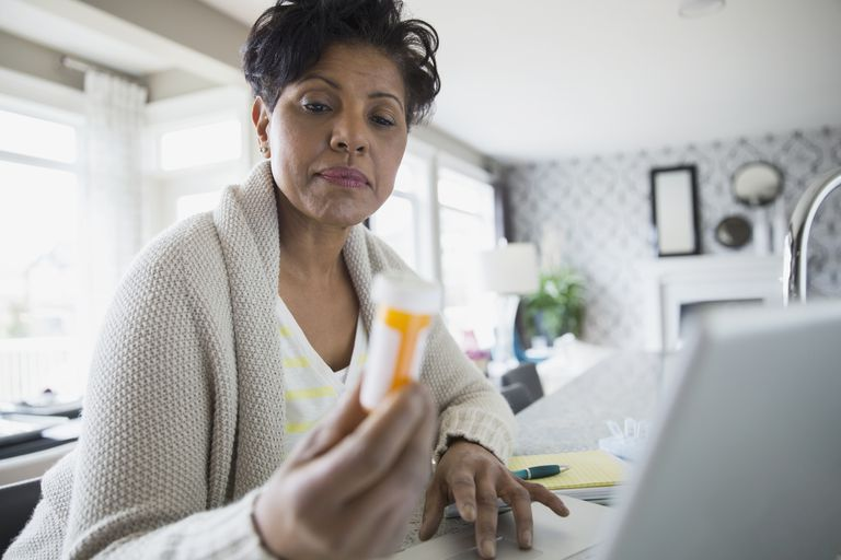 Woman reading prescription bottle label at laptop