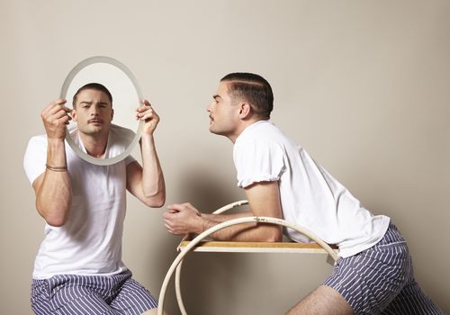 man leaning across a table looking at himself in a mirror held by another man who looks just like him