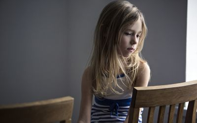sad little girl sitting in chair