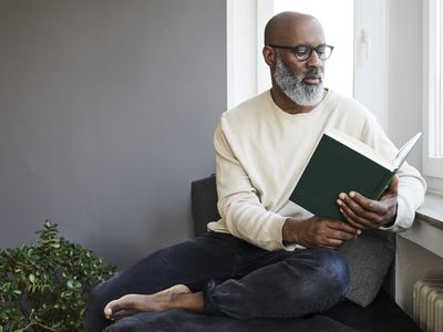 Mature man sitting at window, reading a book