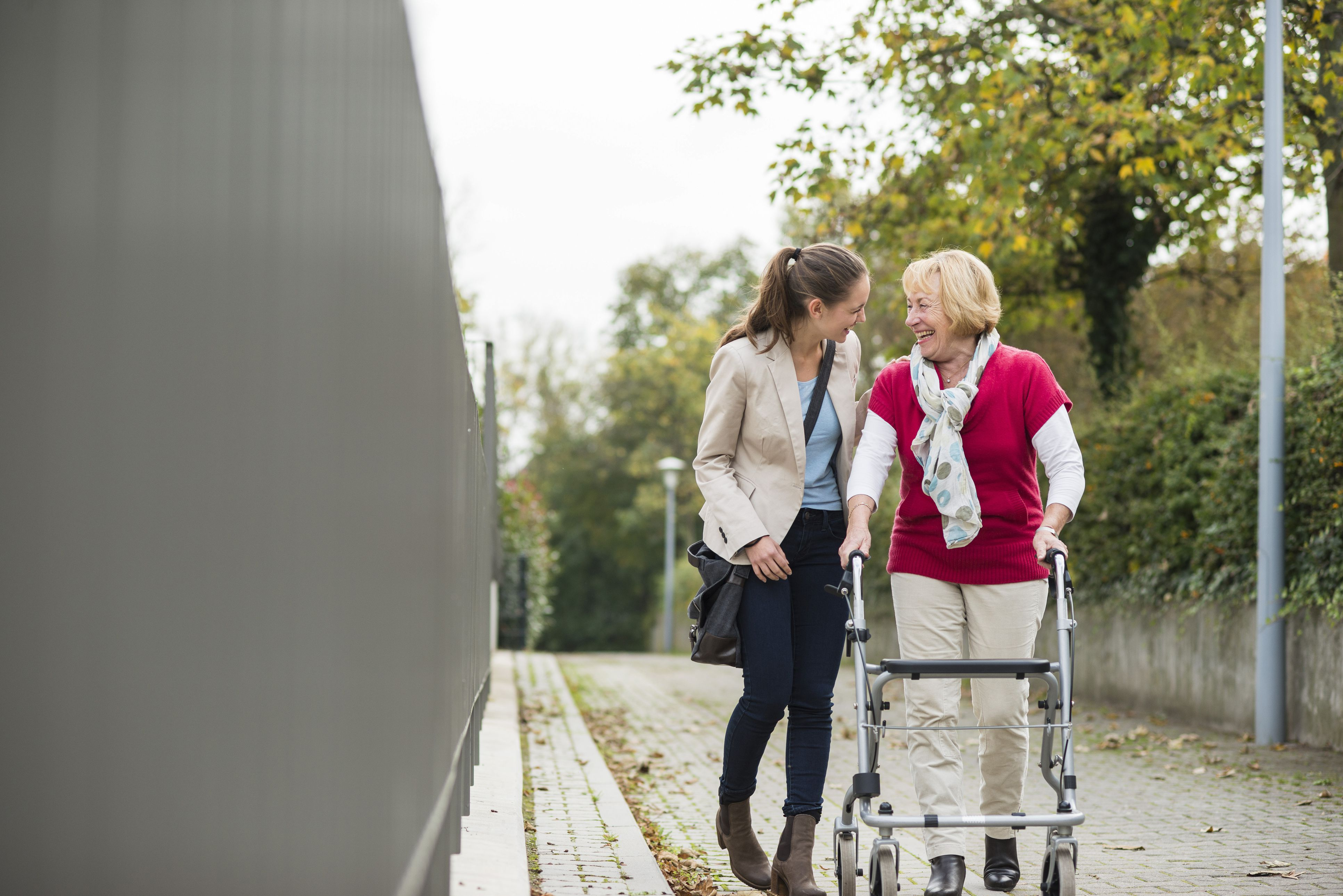 Young woman walking outside with grandmother using walker