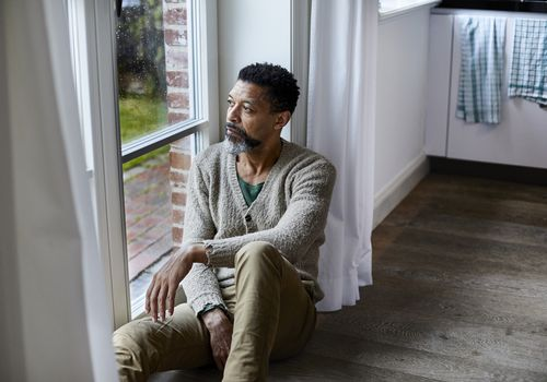 man sitting on the floor looking out of window