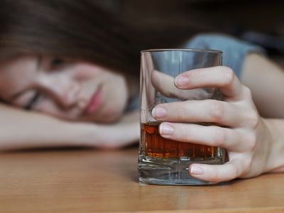 depressed woman with alcohol in her hand