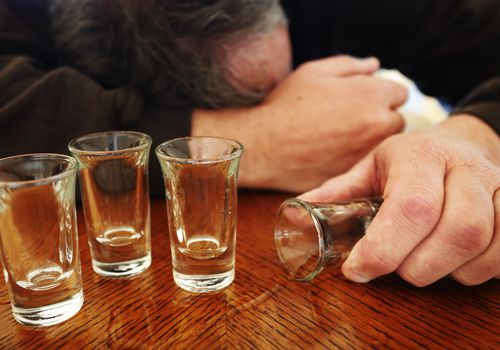 Alcoholism, shot glasses, mature man passed out.