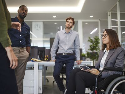 Disabled business woman in wheelchair chatting with coworkers in office