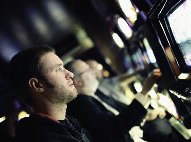Gambler with blank look at slot machine
