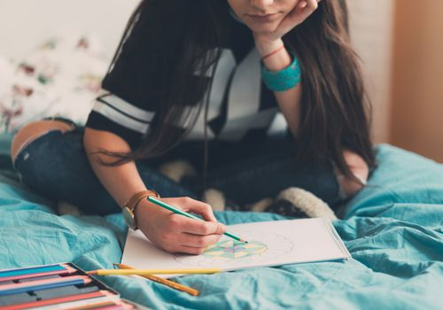 Young woman on a bed coloring with colored pencil