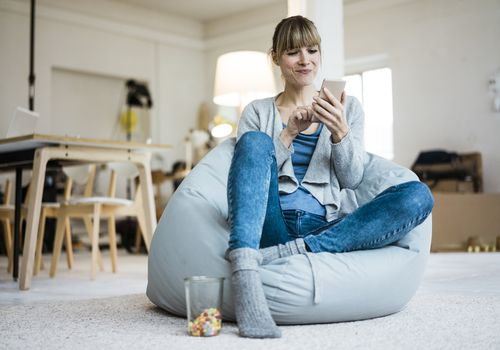 woman on beanbag looking at her phone