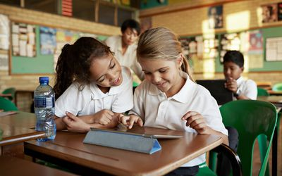 two elementary school girls using tablet in classroom