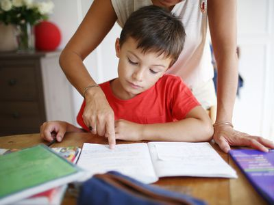 A 7 years old boy doing his homework with his mom
