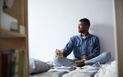 man drinking a cup of tea and smiling