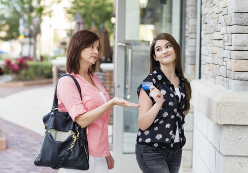 mother holding her hand out for teen daughter to give back credit card in front of store