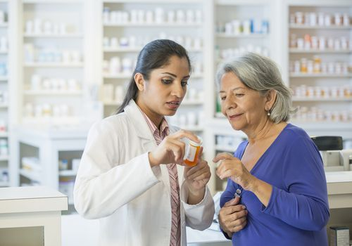 Pharmacist talking to a senior woman about medication