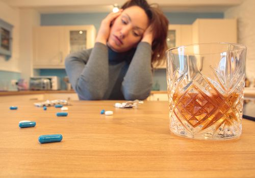 Woman sitting at a table with a glass of alcohol and pills scattered on a table