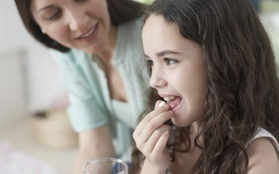 Woman helping young girl take medicine