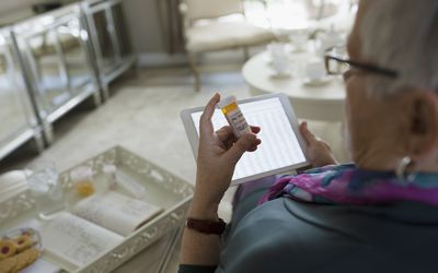 Senior woman reading pill bottle and using tablet