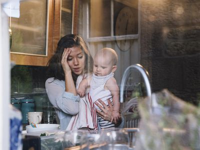Woman holds baby in a kitchen