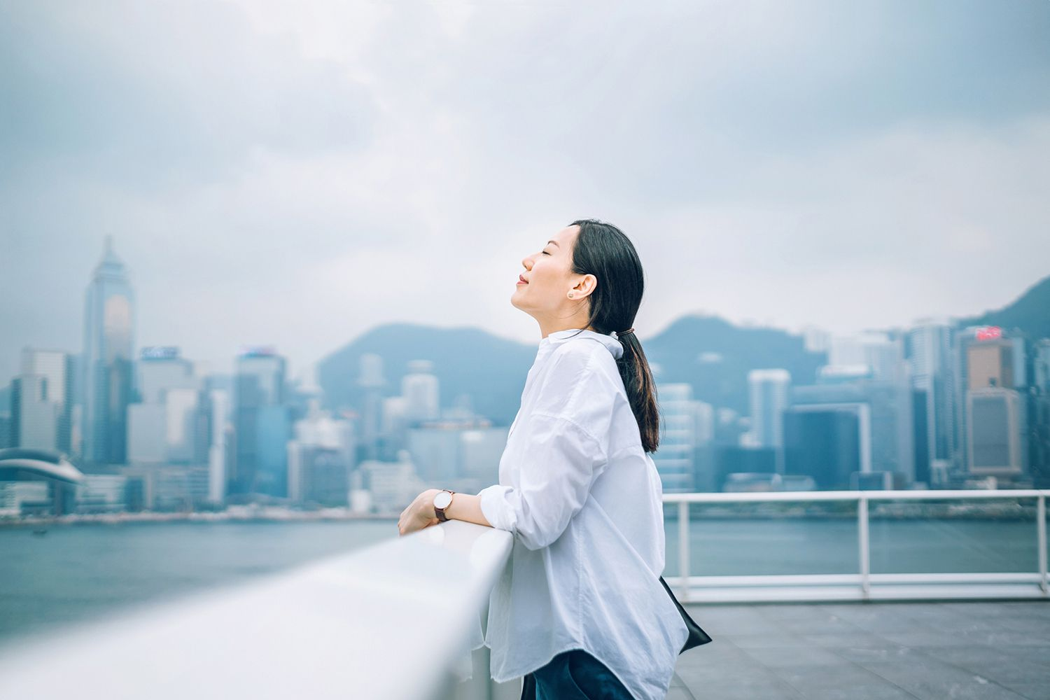 Woman taking deep breath outdoors with cityscape in the background