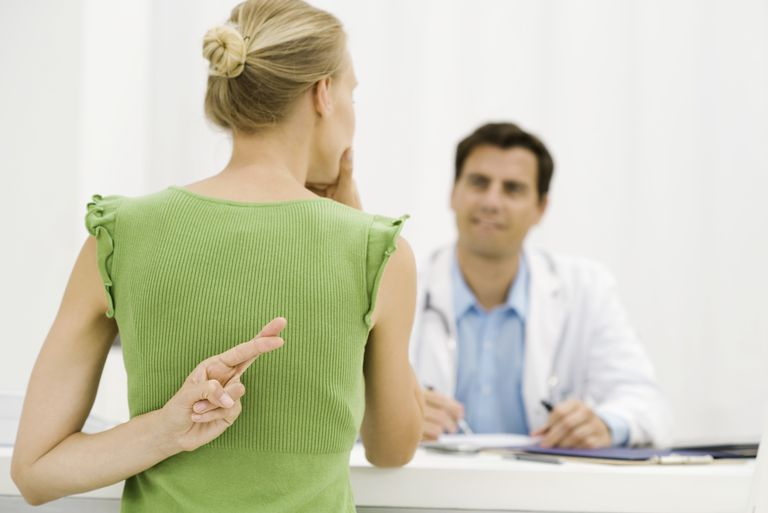 Woman talking to doctor with fingers cross behind her back
