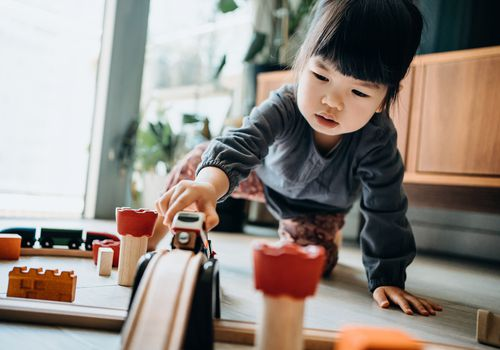Cute little Asian girl playing with wooden toy train in the living room at home