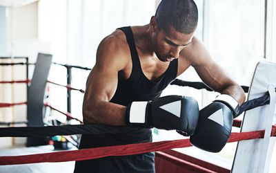 man looking sad at the edge of a boxing ring