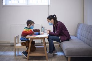Six year old boy working with a psychologist at the psychotherapy session.
