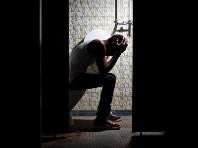 upset sick man sitting on toilet