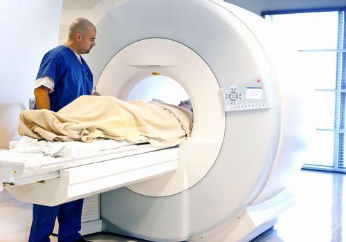 medical professional putting patient in MRI scan machine