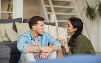 Warm toned portrait of modern young couple talking to each other sincerely while sitting on floor in cozy home interior, copy space