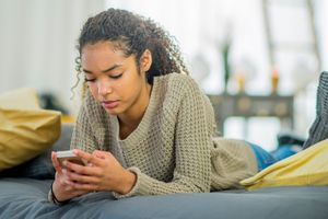 Young girl using her phone while lying down