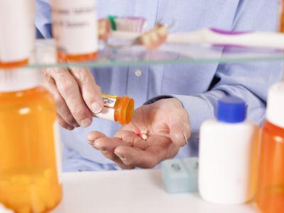 Man Taking Pills From Bottle