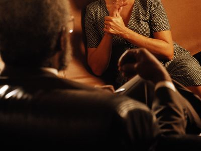 Woman sitting on sofa, looking pensive, listening to man in foreground