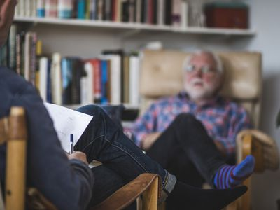 A man, sitting in a chair, talking to his psychiatrist