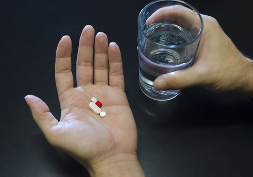 Hands holding three pills and a glass of water against black background, copy space