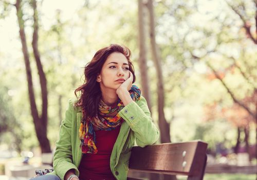 Woman sitting on a park bench with a thoughtful expression.