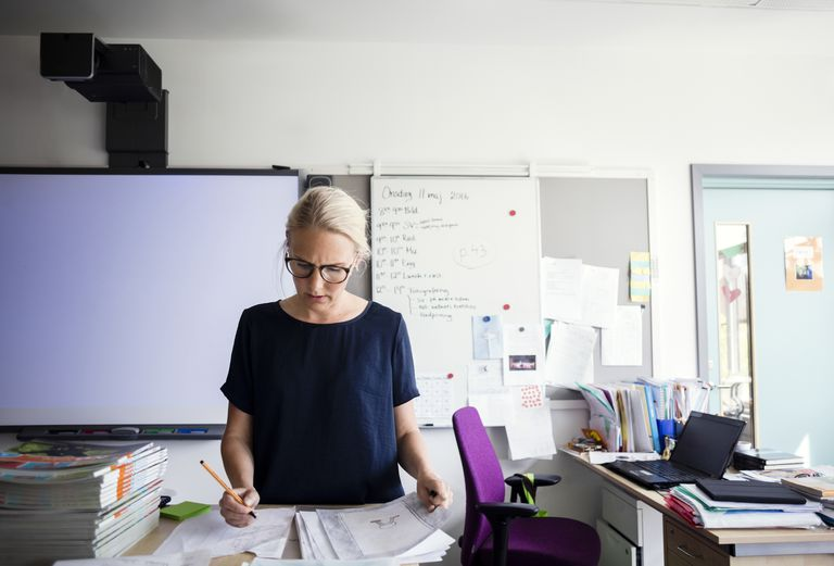 Teacher examining papers against blank whiteboard in classroom