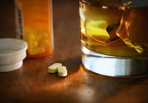 Two large pills next to a glass of alcohol.