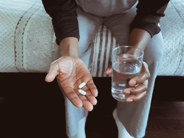 Person sitting down holding a glass of water and pills.