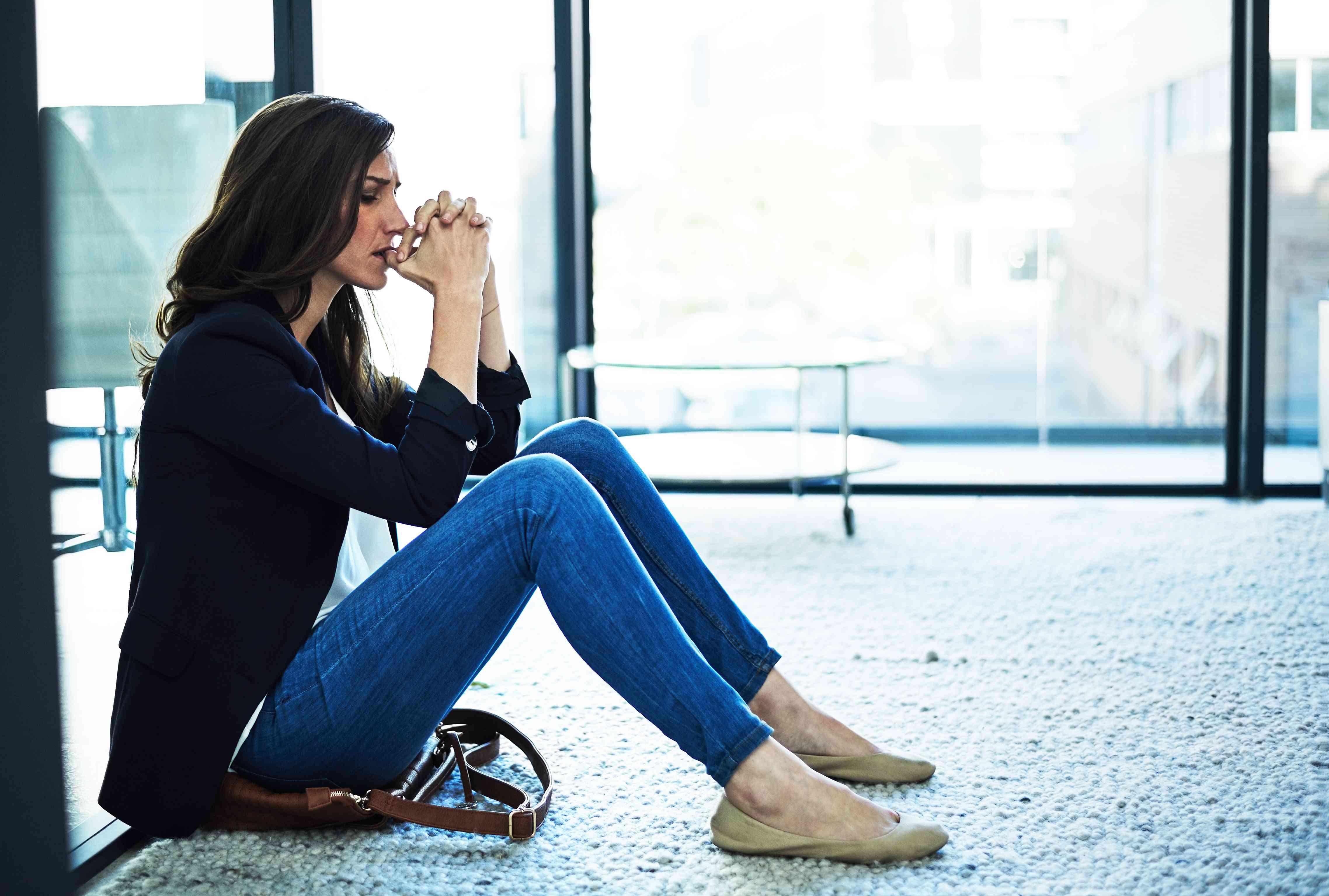 Anxious woman sitting on the floor