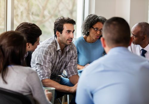 Vulnerable mid adult man talks in group therapy meeting