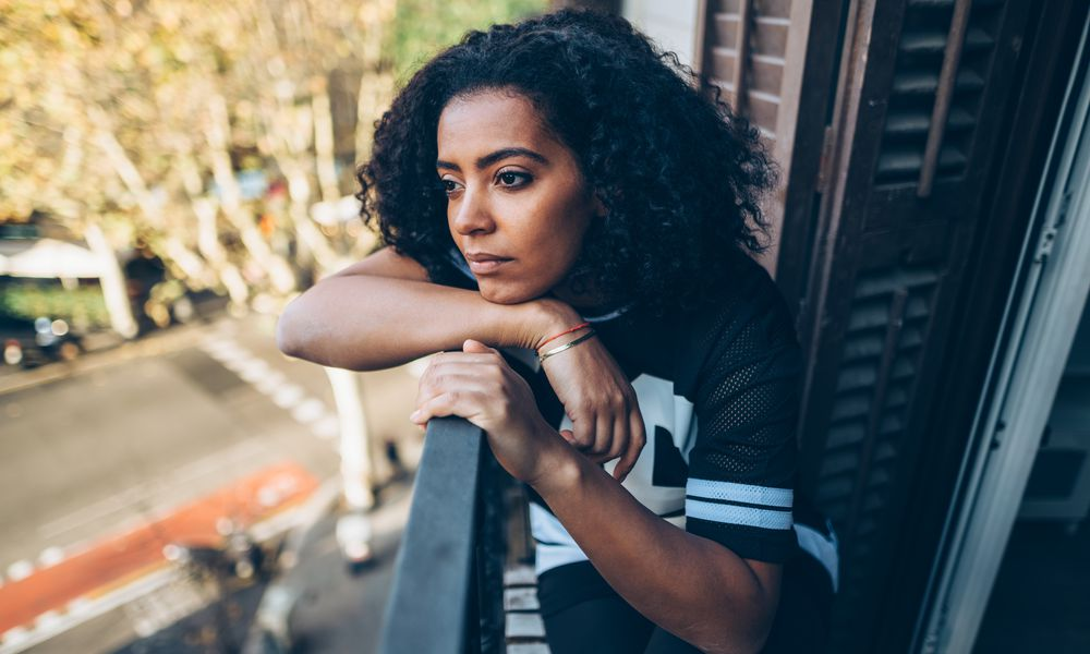 Sad BIPOC woman looking out the winddow