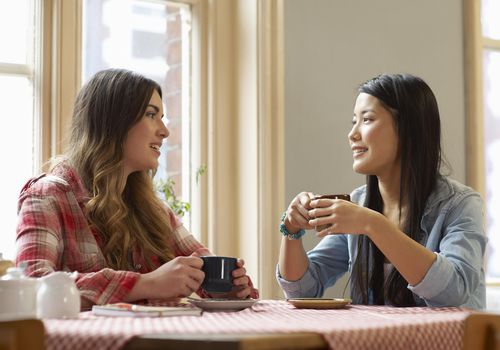 Two women talking together in cafe.