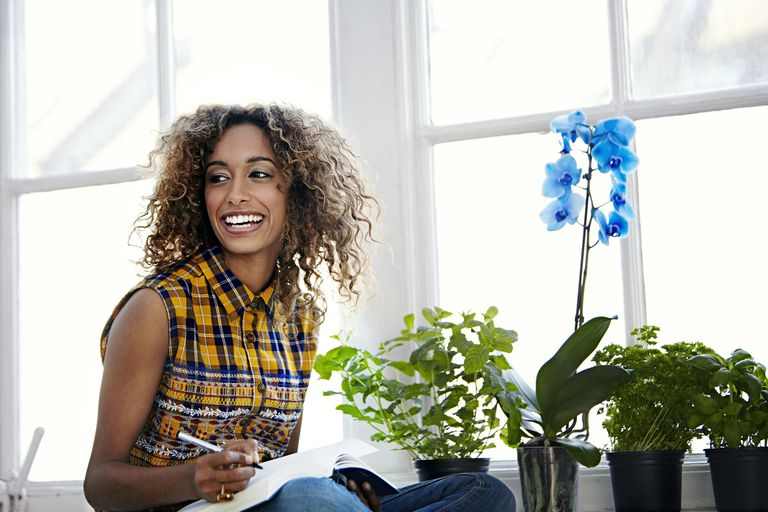 Woman working surrounded by plants and flowers.